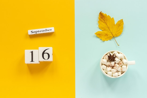 Autumn composition. wooden calendar september 16, cup of cocoa with marshmallows and yellow autumn leaves on yellow blue background. top view flat lay mockup concept hello september.