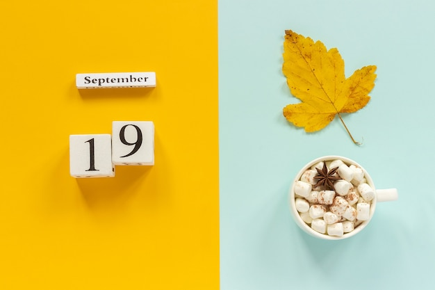 Autumn composition. wooden calendar september 19, cup of cocoa with marshmallows and yellow autumn leaves on yellow blue background. top view flat lay mockup concept hello september.