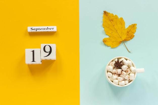 秋の構成。木製のカレンダー9月19日、マシュマロと黄青色の背景に黄色い紅葉とココアのカップ。上面図フラットレイモックアップコンセプトこんにちは9月。