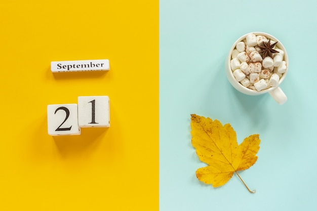 Autumn composition. wooden calendar september 21, cup of cocoa with marshmallows and yellow autumn leaves on yellow blue background. top view flat lay mockup concept hello september.