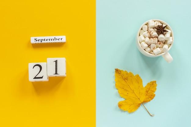 秋の構成。木製のカレンダー9月21日、マシュマロと黄青色の背景に黄色い紅葉とココアのカップ。上面図フラットレイモックアップコンセプトこんにちは9月。