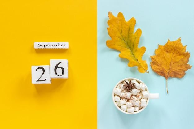 秋の構成。木製のカレンダー9月26日、マシュマロと黄青色の背景に黄色い紅葉とココアのカップ。上面図フラットレイモックアップコンセプトこんにちは9月。
