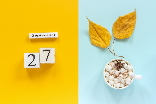 Autumn composition. wooden calendar september 27, cup of cocoa with marshmallows and yellow autumn leaves on yellow blue background. top view flat lay mockup concept hello september.