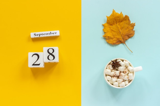 Autumn composition. wooden calendar september 28, cup of cocoa with marshmallows and yellow autumn leaves on yellow blue background. top view flat lay mockup concept hello september.