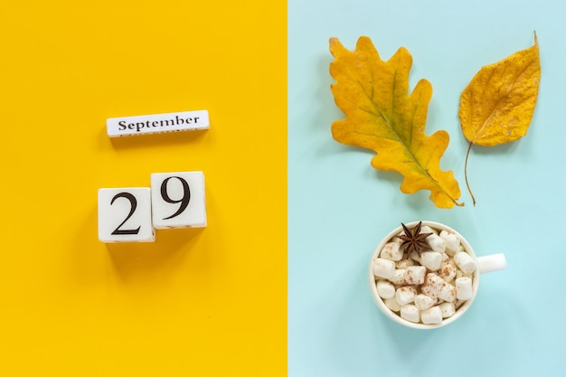 Autumn composition. wooden calendar september 29, cup of cocoa with marshmallows and yellow autumn leaves on yellow blue