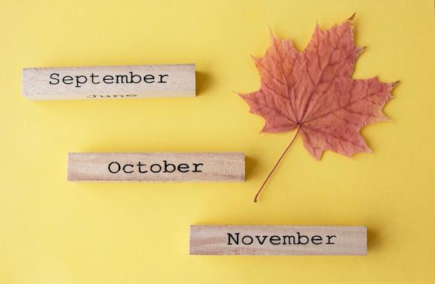Autumn composition wooden calendar yellow maple leaf