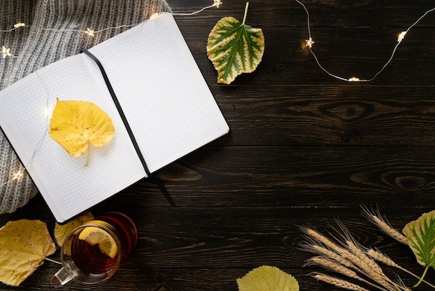 Autumn composition. workspace with notebook, cup of lemon tea, autumn leaves and fairy lights. top view, flat lay on black wooden background