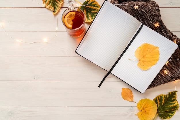 가을 구성. 노트북, 레몬 차 한잔, 단풍 및 요정 조명이있는 작업 공간. 평면도, 평면 흰색 나무 배경에 누워