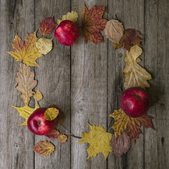 Autumn composition. wreath made of autumn leaves and red apples on old wooden background