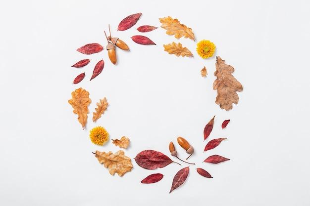 秋の構成。秋の赤と金の葉、花、どんぐりで作られた花輪。サークル秋のモックアップ、フラットレイ、上面図、コピースペース