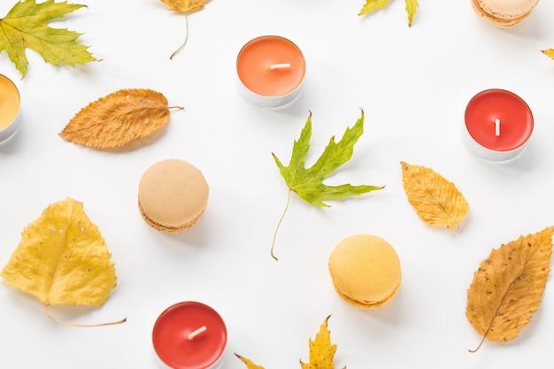 秋の構成黄色の葉キャンドルと白い背景のマカロン秋のハロウィーンのコンセプト