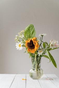 秋のコンセプト。花瓶に枯れたドライフラワーとヒマワリの花束