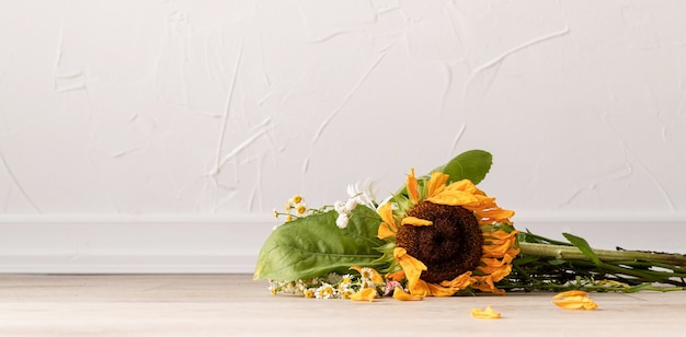 秋のコンセプト。枯れた花の花束と床にひまわり。バナー