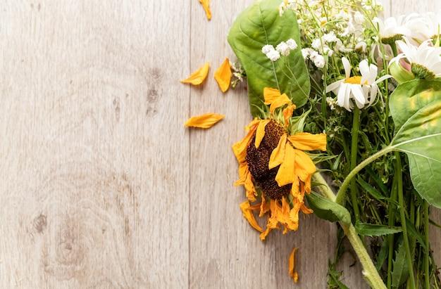 秋のコンセプト。枯れた花の花束と床にひまわり。フラットレイ