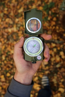 Autumn concept. autumn travel. compass in a male hand