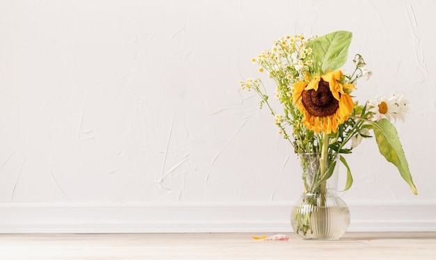 Autumn concept. a bouquet of withered flowers and a sunflower in a vase