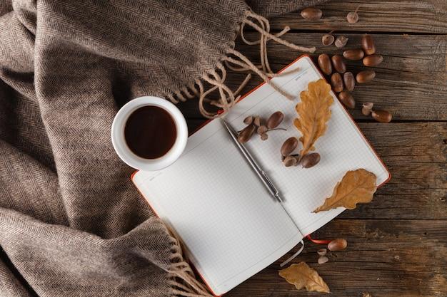 秋のコンセプト、色鮮やかな葉、ドングリ、一杯のコーヒーと木製のテーブル、トップビューでニットスカーフ