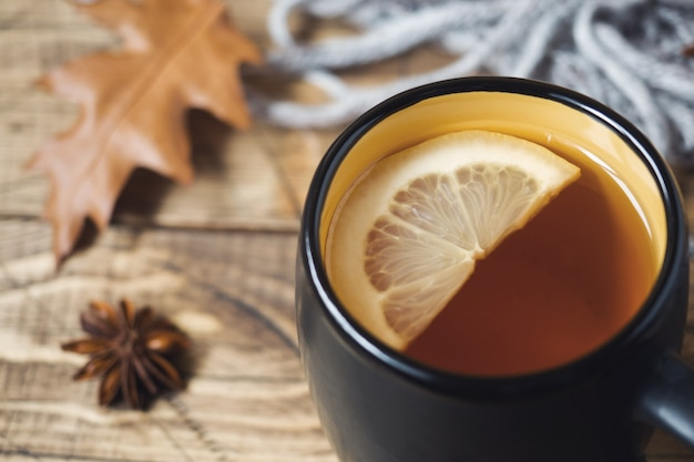 Autumn concept. cup of tea, warm blanket and yellow leaves on wooden table.