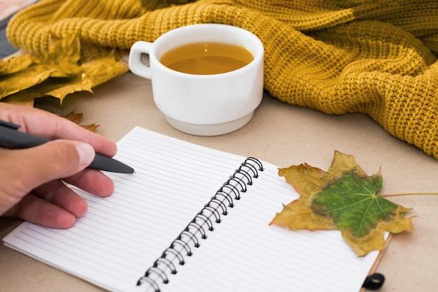 秋のコンセプト。空白のノートに手書きで書き込みます。一杯のお茶、セーター、カエデの葉。