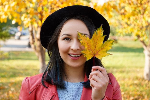 Autumn concept portrait of a girl woman in a hat and red jacket