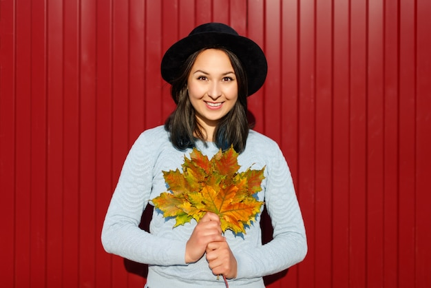 Autumn concept. portrait of a young woman in a hat and a blue blouse with autumn maple leaves.