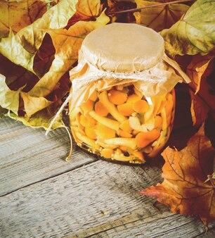 秋のコンセプト。木の板のガラス瓶に保存された食品。マリネしたきのこ