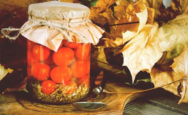 秋のコンセプト。木の板のガラス瓶に保存された食品。トマトのマリネ