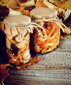 秋のコンセプト。木の板のガラスの瓶に保存された食品。マリネしたきのこ