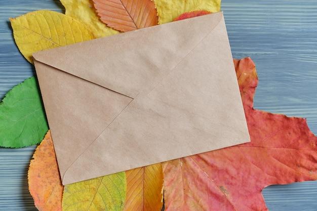 乾燥した葉にクラフト封筒と秋のコンセプト