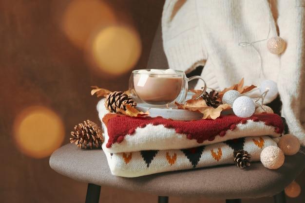 Осенняя концепция со свитерами, чашкой кофе и размытыми огнями