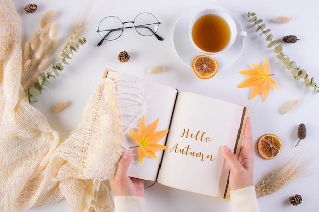 Осенняя концепция. женщина открыла книгу на столе с текстом здравствуйте, осень.