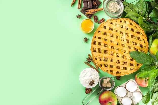 甘いアップルパイと秋の料理のベーキングの背景。新鮮なリンゴ、シナモン、スパイス、ベーキング材料、薄緑色の背景に上面のコピースペースと伝統的なアメリカのアップルパイ