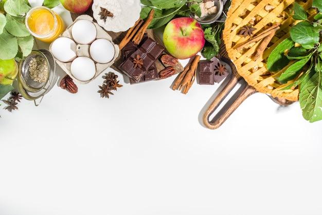甘いアップルパイと秋の料理のベーキングの背景。新鮮なリンゴ、シナモン、スパイス、ベーキング材料、白い背景の上のビューコピースペースと伝統的なアメリカのアップルパイ