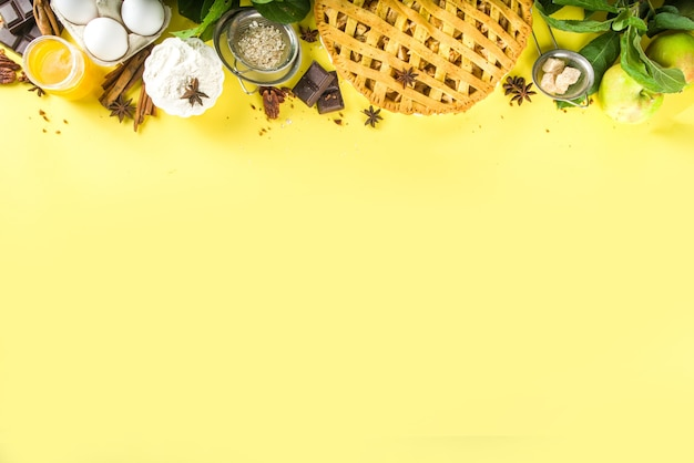 甘いアップルパイと秋の料理のベーキングの背景。新鮮なリンゴ、シナモン、スパイス、ベーキング材料、黄色の背景に上面のコピースペースと伝統的なアメリカのアップルパイ