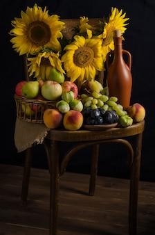 秋の宝庫。暗いスタイルで黒い表面に果物、ブドウ、ワインのヒマワリのある静物。感謝祭と収穫。