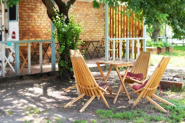 Autumn courtyard interior with garden furniture. empty sun loungers and table on veranda of house