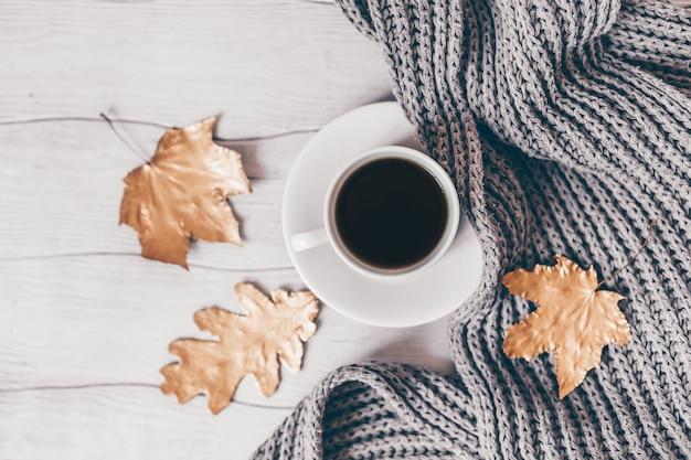 . осенняя уютная чашка кофе композиции и золотые листья на белом деревянном столе. вид сверху. плоская планировка.