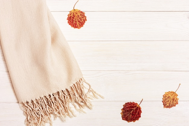 Autumn cozy composition with dried leaves of aspen and pastel beige scarf on wooden background