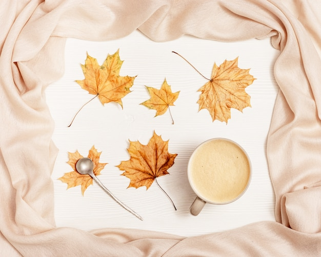 Autumn cozy composition with dried leaves of maple and pastel beige scarf and coffee