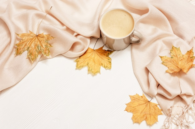 Autumn cozy composition with dried leaves of maple, pastel beige scarf and cup of coffee on white wooden surface