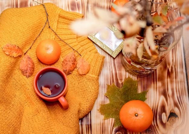 秋の居心地の良いフラットレイ構成。ニットの黄色いセーター、ホットチョコレートの蒸しカップ、みかん、紅葉の花束。居心地のよさの秋または冬の概念。