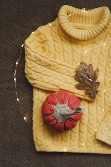 Осенний уютный натюрморт с листьями тыквенного свитера ручной работы и теплыми огоньками