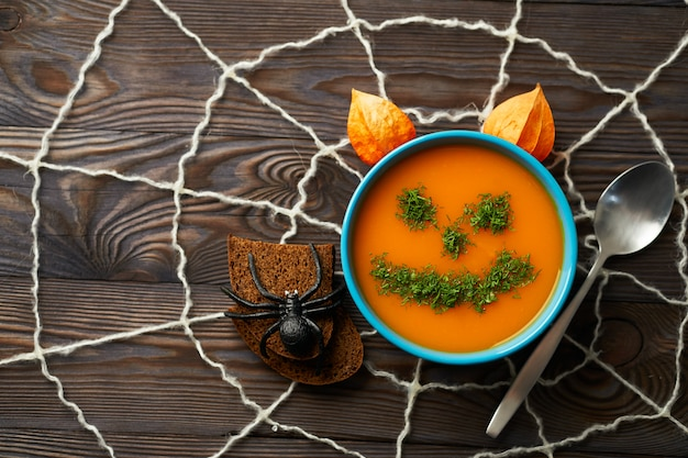 Autumn cream soup garnished with dill in the form of funny faces halloween pumpkins.