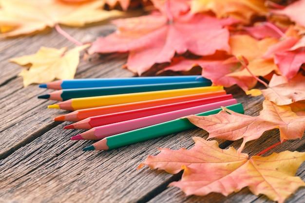 Осенний творческий художественная роспись фон с карандашами и кленовыми листьями