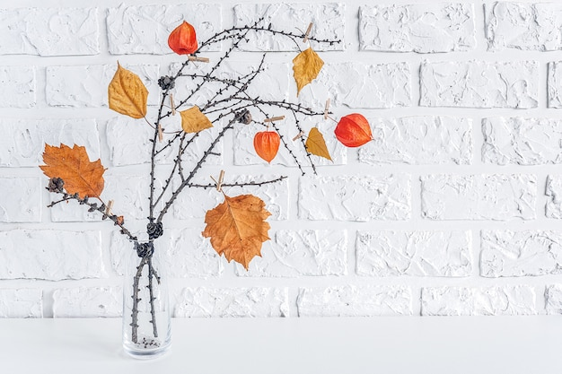 Autumn creative bouquet of branches with yellow leaves on clothespins in vase on table background white brick wall