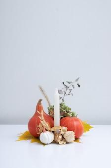 カボチャの秋の創造的な静物、コピースペース付きキャンドルとドライフラワー