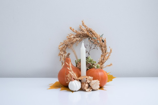 カボチャの秋の創造的な静物、キャンドルとドライフラワー