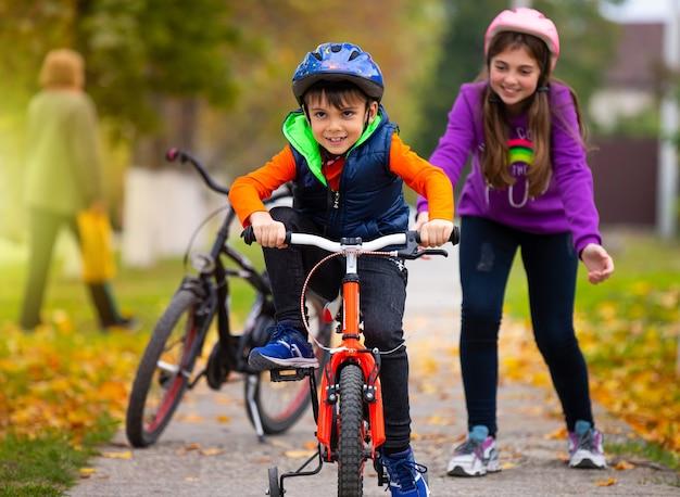 Осенний день. сестра учит младшего брата кататься на велосипеде и радуется его успехам. семья и здоровый образ жизни.