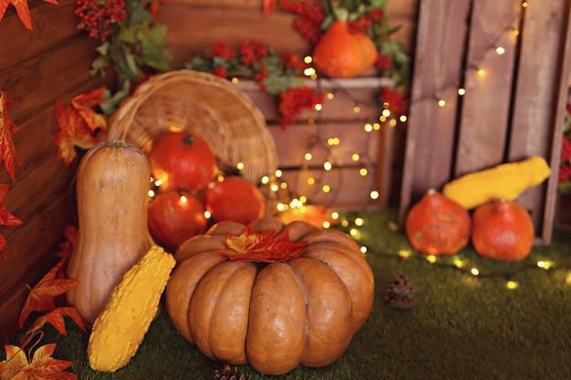 秋の装飾:カボチャ、果実、木製の背景の葉、感謝祭やハロウィーン
