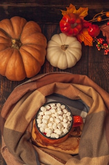 Autumn decor on a wooden background: a mug with cocoa and marshmallows, a checkered scarf, pumpkins and autumn leaves, top view flat lay